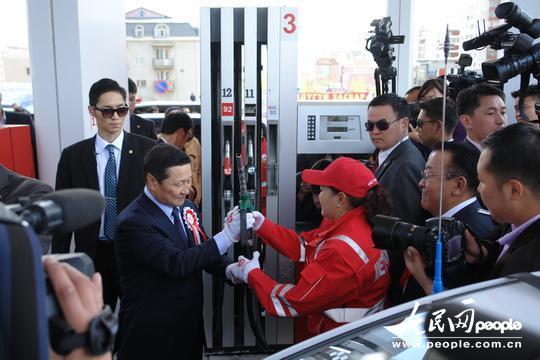 """蒙总理阿勒坦呼雅格(前排左一)为""""蒙古93""""汽油首个用户""""乌兰巴托出租车公司""""司机冈巴特尔的汽车加油。"""
