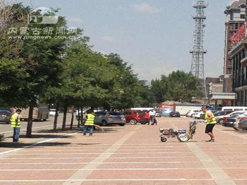 阿拉善南路香槟美景门前,工作人员正在施划免费停车位-呼和浩特市