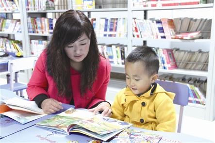 ●小学生在家长的陪伴下在少儿图书室写作业-乌审旗全民尽享文化大繁荣