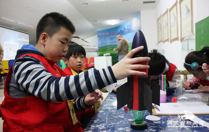 """用废弃的饮料瓶制作动力舱   本网讯(记者 赵静)4月12日,是""""国际载人航天日"""",呼和浩特市30多名小学生在内蒙古博物院亲手制作水火箭,共同揭开了火箭当中蕴含的秘密。   活动中,孩子们利用学到的物理现象,分组制作水火箭。具体为:首先用废弃的饮料瓶制作成动力舱、箭体、箭头、尾翼,再灌入三分之一的水,利用打气筒充入空气到达一定的压力后发射。通过动手制作和演示,孩子们直观了解了火箭的发射升空的过程,在游戏中学到了航天知识。   此外,内蒙古博物院讲解员还结合""""飞天神舟&"""