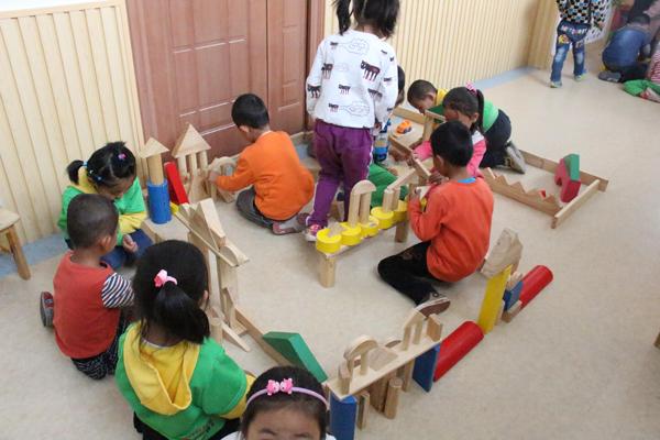 大班的孩子们用木制积木进行合作搭建