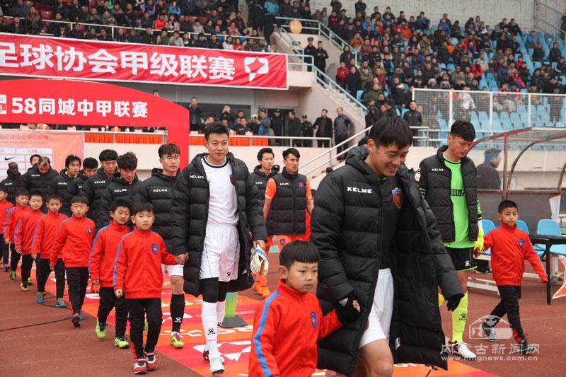 球员入场。   本网讯 (记者 巴菊媛) 3月12日,2016年中国足球协会甲级联赛在青岛拉开战幕。在首轮比赛中,呼和浩特职业足球队客场对决青岛中能队,最终经过90分钟的争夺,呼和浩特队以0:1小负对手。 记者在天泰体育场南侧看台看到,约20余人的青城狼球迷在寒冷的天气下为呼和浩特队呐喊助威,使得场上又多了一份来自草原的温暖。据了解,这些球迷当中,不仅有从呼和浩特市专程来到青岛观战的球迷,还有许多身在青岛工作与学习的呼和浩特人。   开场第2分钟,中能队率先获得一颗前场任意球。但呼和浩特队打出反击,获得