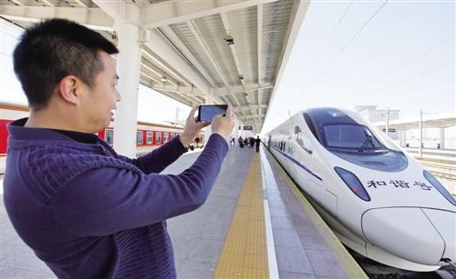 在东胜西站下车的乘客用手机拍摄首次开行的呼和浩特东至鄂尔多斯图片