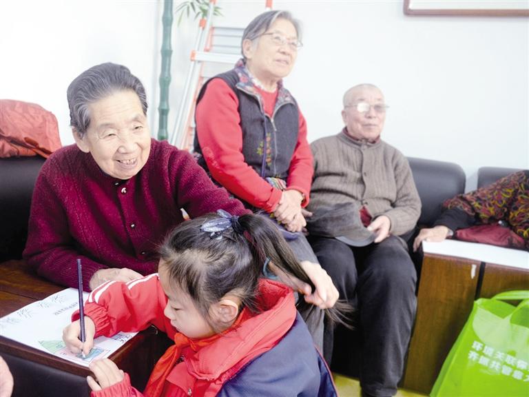 """""""1月16日,小学生张舒雯一边画画一边对身边的丁秀兰老人甜甜地说."""