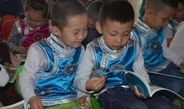 随着老师一声喊,幼儿们蜂拥上前,向志愿者和老师们鞠躬行礼,接受赠书.
